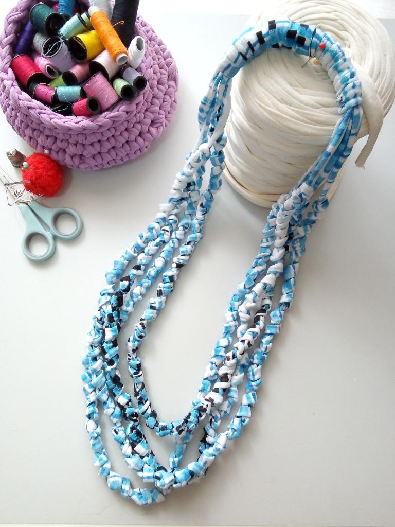 Sciarpa collana cucita a mano nei colori latte, celeste e nero. Ha quattro fili di fettuccia di cotone poco elasticizzata annodati pazientemente.